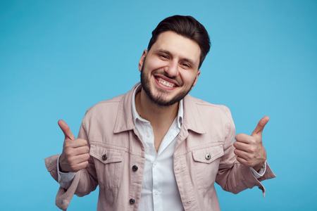 Headshot of handsome young male wearing pink stylish jeans jacket, smiling and showing thumb up over blue background. Foto de archivo - 124961611