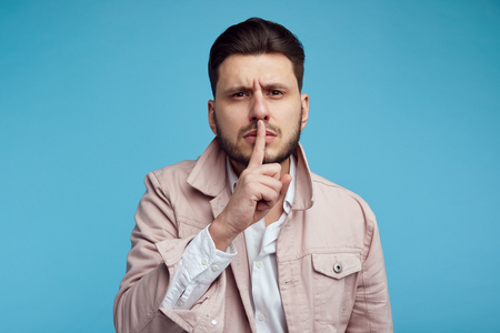 Attractive man shows hush gesture, looks with stunned expression at camera, afraids of gossiping, isolated over blue background.