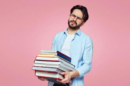 Unshaven student with a tired face holding a bunch of books and preparing for his upcoming exams, isolated over pink background.