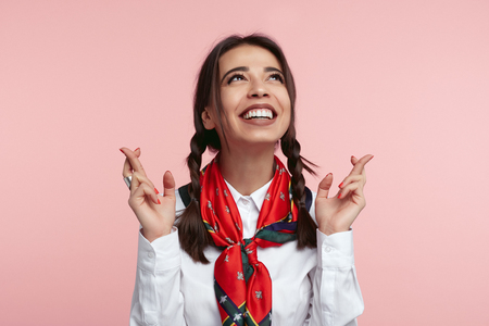 Happy young lady has funny glad expression, looks up and keeps fingers crossed for good luck, dressed in white shirt and scarf