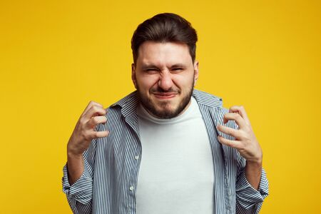 Young annoyed male gestures angrily, expresses negative emotions, dressed in casual blue shirt, poses against yellow studio wall. Banco de Imagens