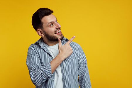 Cheerful handsome man wearing classic shirt with lines and pointing happily away on orange background. Фото со стока