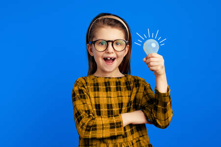 Girl with light bulb smiling while having brilliant idea against blue wall