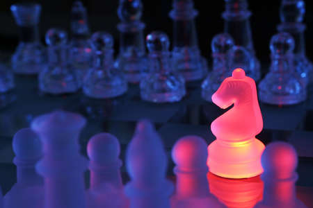 Closeup shot of a chessboard with knight highlighted by red light. photo