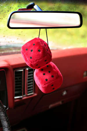 Fuzzy red dices hanging on the rear view mirror Imagens