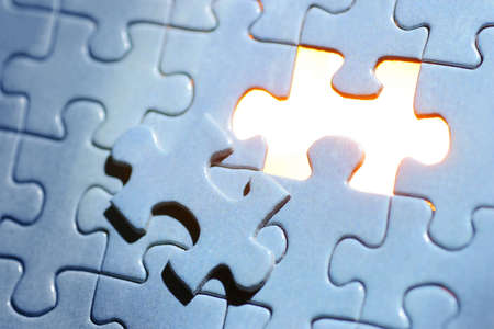 jigsaw puzzle: A blue jigsaw puzzle missing one piece with golden light showing through.