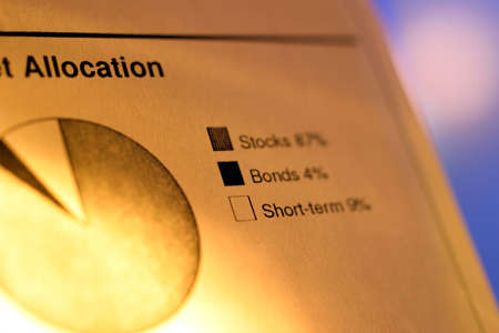 A closeup of a financial chart with pie graph. Graph legend reads: Stocks, Bonds, Short-term. Shallow depth of field with focus on graph legend.