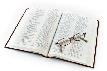study: Open bible with folded reading glasses. Focus on glasses.