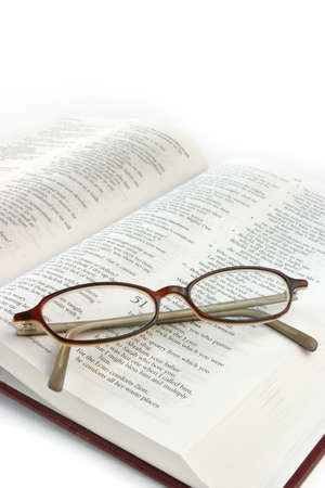Open bible with folded reading glasses. Focus on glasses.