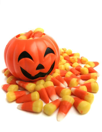 A plastic pumpkin filled with candy corn.