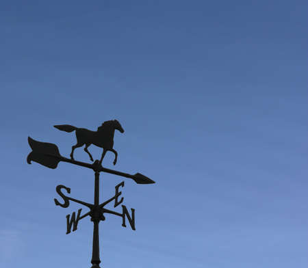Rooftop weather vane against a clear blue sky. Stock Photo - 4409421