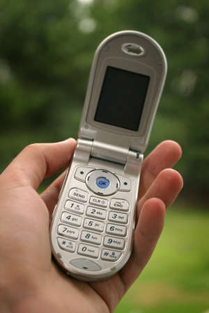 flip phone: A hand holding a cellphone. Shallow depth of field with focus on top of keypad. Stock Photo