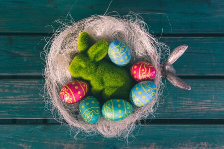 Chocolate multi colored Easter eggs in a basket, green easter bunny, green bench, easter decoration, Amsterdam the Netherlands Stock Photo - 133971183