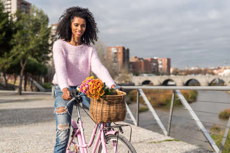 Black happy young woman riding a vintage bicycle with beautiful basket of flowers