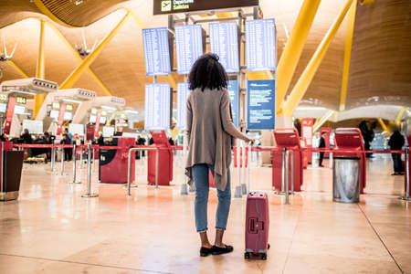 Vrouw die het paneel van de tijdschemainformatie in de luchthaven met een koffer bekijkt Stockfoto