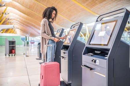 glückliche schwarze Frau, die den Check-in Automaten am Flughafen verwendet, der die Bordkarte erhält.