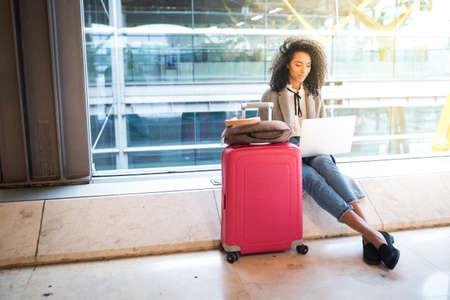Mujer negra que trabaja con la computadora portátil en el aeropuerto que opera en la ventana Foto de archivo - 87730832