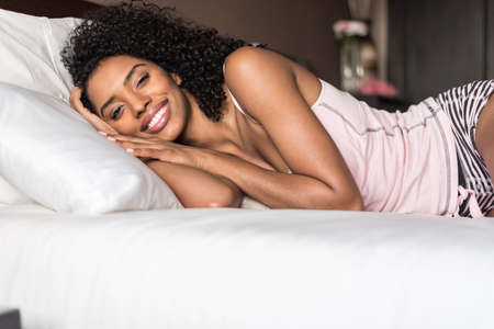 woman happy on bed smiling and stretching looking at camera Stock Photo