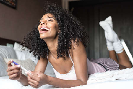 happy woman on bed with a pregnancy test