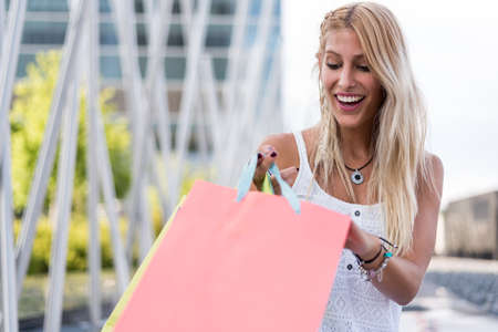 sun energy: Blonde happy young woman shopping with bags outdoors.