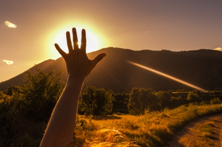 Girl raising her hand in front of the sun and the mountains photo