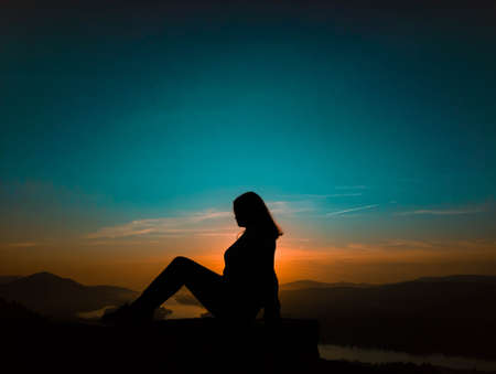 A woman sitting in profile at sunset