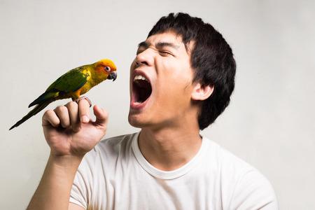 Asian men with parrot - Sun Conure photo