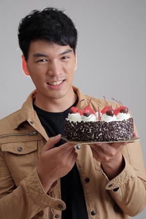 Asian man with birthday ice-cream cake on fire