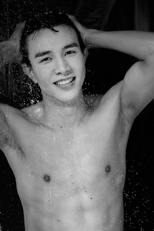 nude male body: Asian man take a shower in the dark Stock Photo
