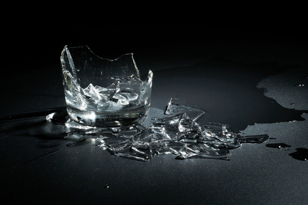 A breaking glass of water on the black background