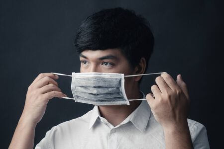 Asian man with medical mask on his face in black background - Studio portrait Stock Photo - 144016422