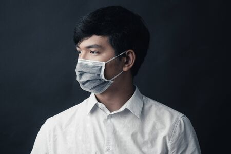 Asian man with medical mask on his face in black background - Studio portrait