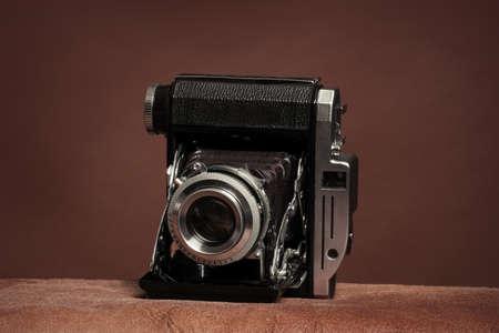 vintage rangefinder film folding camera on brown background