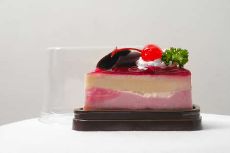 a piece of strawberry jelly cheesecake in the take away plastic box