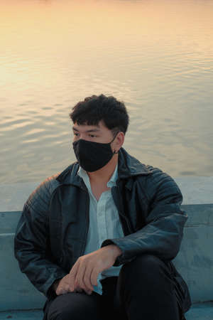 Asian man sit at riverside with black fabric face mask