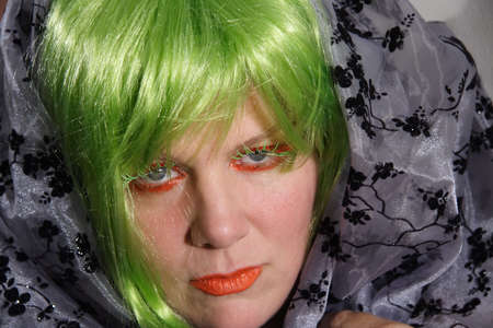 headress: Woman in Green Wig and Orange Make-up Stock Photo