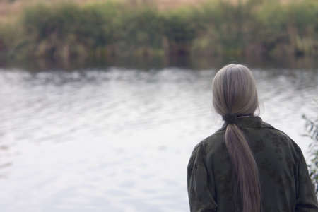 A senior woman  is enjoying a lakes beauty.