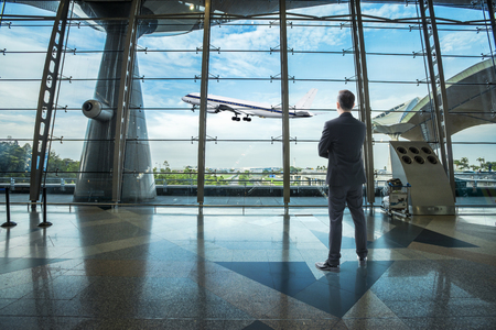 Businessman standing in the airport looking toward outdoor aeroplane with nice sky