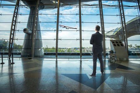 Businessman standing in the airport looking toward outdoor airplane with nice sky