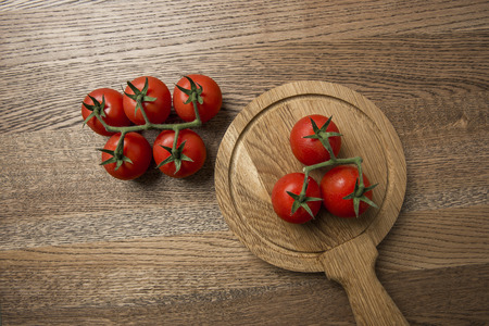 Fresh tomatoes presented on wooden round and nice texture background