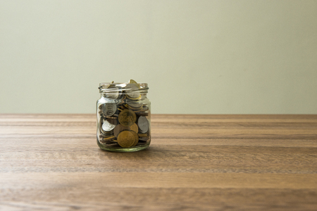 Coins in a jar on wooden table