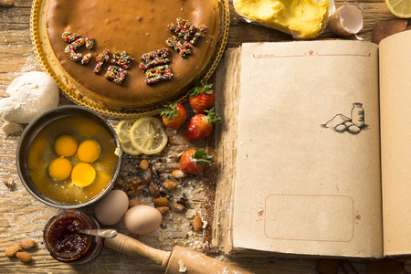 오래 된 빈 책과 케이크 재료 (딸기, 계란, 밀가루, 우유, 버터, 설탕)를 베이킹 농촌 빈티지 나무 주방 테이블. 무료 레시피 텍스트 공간이있는 배경 레 스톡 콘텐츠