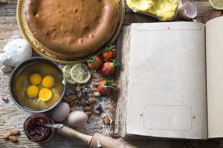 Rural vintage wooden kitchen table with old blank book and baking cake ingredients (strawberry, eggs, flour, milk, butter, sugar). Background layout with free recipe text space. Reklamní fotografie