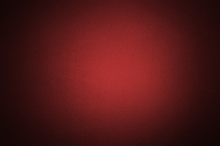 Red colour paper with texture useful as a background vignetted and gradient background