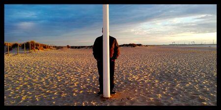 Person hidden behind a pole