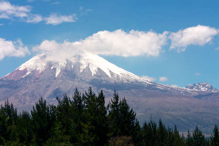 Cotopaxi volcano in Ecuador, blue sky with few clouds behind the mountains a spring day