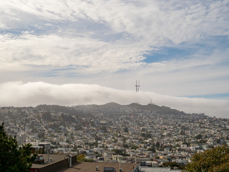 View of fog overtaking Sutro Tower and Twin Peaks in San Francisco. These spots are big on tourism.