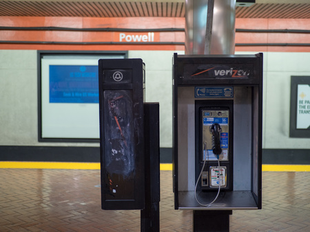 SAN FRANCISCO, CA - MARCH 31, 2018: An unkempt payphone in a train tunnel in San Francisco. This is demonstrative of the decline of phone booths over the years. Reklamní fotografie - 113620574