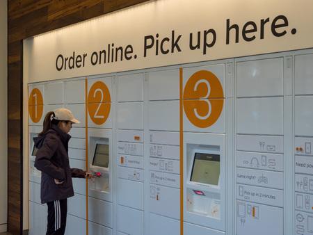BERKELEY, CA - 17. MÄRZ 2018: Eine Frau holt ihr Paket von Amazon Locker im Amazon Store an der University of California, Berkeley's Student Union.