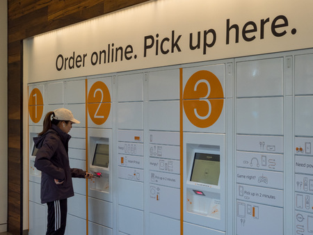 BERKELEY, CA - MARCH 17, 2018: A woman picks up her package from Amazon Locker inside the Amazon Store at the University of California, Berkeley's student union.